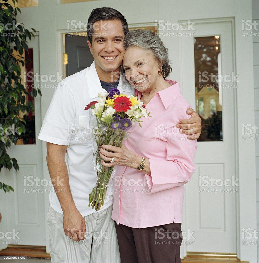 Junger Mann umarmt Großmutter in front of house – Foto