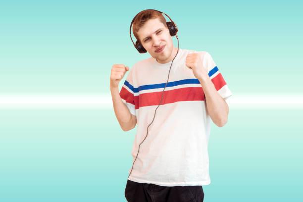ung man känslomässiga i hörlurar lyssna på musik som isolerade - happy indie pop bildbanksfoton och bilder
