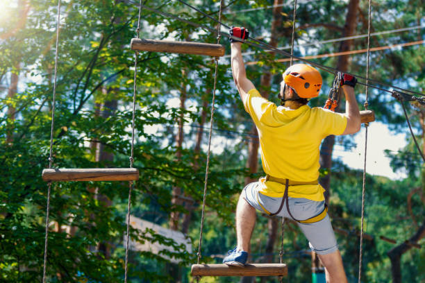 Young man enjoy active leisure in extreme rope park Young male man adult wears protective helmet with action camera having fun in extreme rope park, amusement park. Climbing in rope bridge at green forest. Active healthy lifestyle in spring or summer. zip line stock pictures, royalty-free photos & images