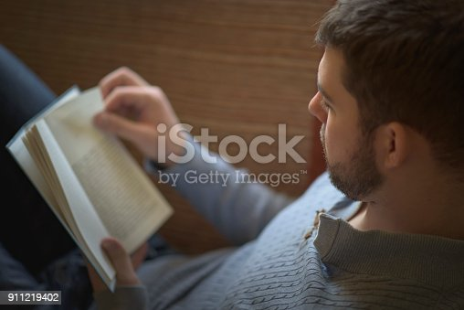 istock Young man enjoying a great book 911219402