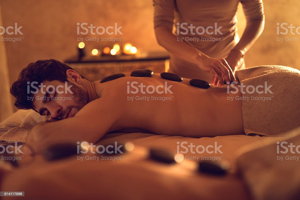 Young man enjoying during hot stone therapy at the spa. stock photo