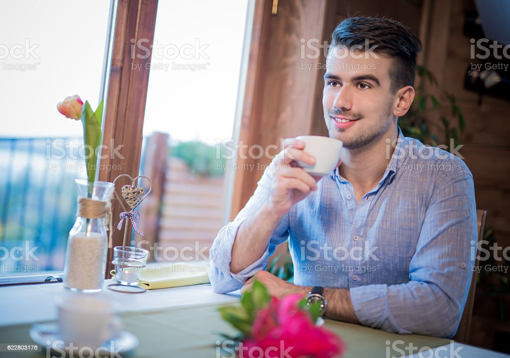 Young man enjoying his coffee on a meeting stock photo