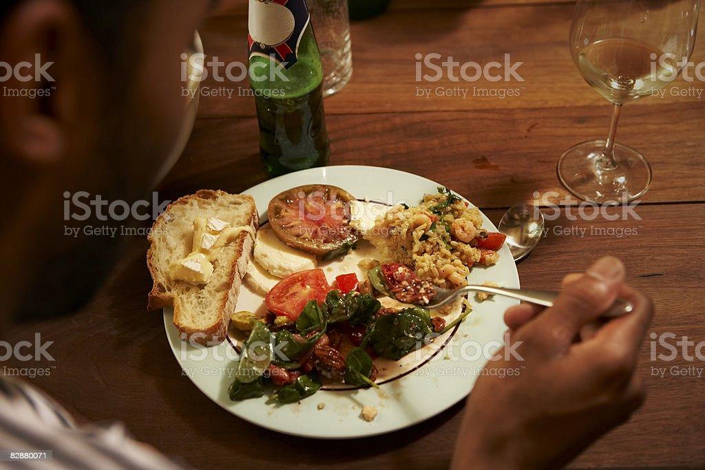 Young man enjoying home cooked meal royaltyfri bildbanksbilder