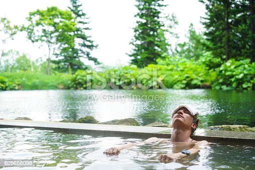 Front view of young man with white towel on his head while lying and enjoying hot mineral water in outdoor onsen (hot spring) near Niseko on Hokkaido. In background are trees and grey sky of cloudy and rainy weather.  This is traditional way of having bath in Japan.