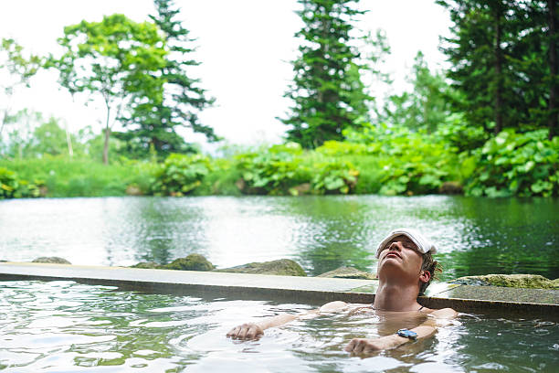 young man enjoying hot spring water on hokkaido, japan - hot spring stock photos and pictures