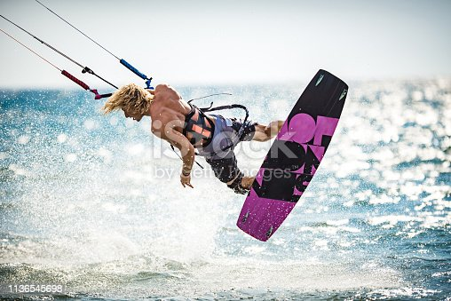 Athletic man having fun while kitesurfing on the sea.