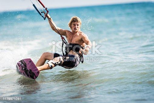 Athletic man having fun while kitesurfing on the sea. Copy space.