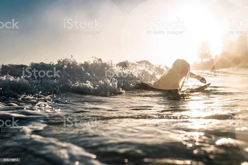 Young man enjoying into the sea and learn surfboarding stock photo