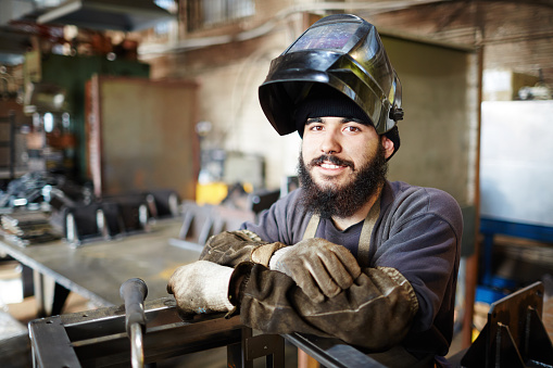 Smiling handsome young craftsman in welding helmet leaning on constriction frame and looking at camera