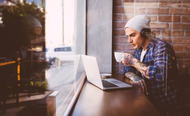 junger mann musik genießen, kaffee trinken, arbeiten auf seinem laptop - kaffeetasse tattoo stock-fotos und bilder
