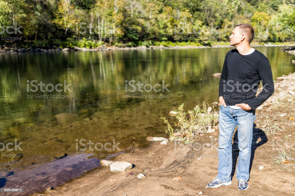 Young man enjoying nature looking at peaceful, calm river lake during sunny autumn day with reflection stock photo