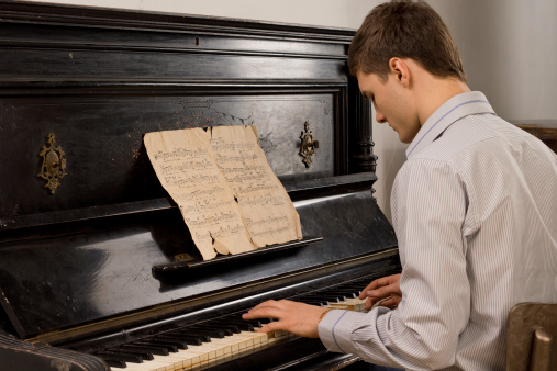 Young man enjoying playing an old melody