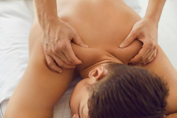 Young man enjoying relaxing body massage done by professional masseur in spa salon stock photo