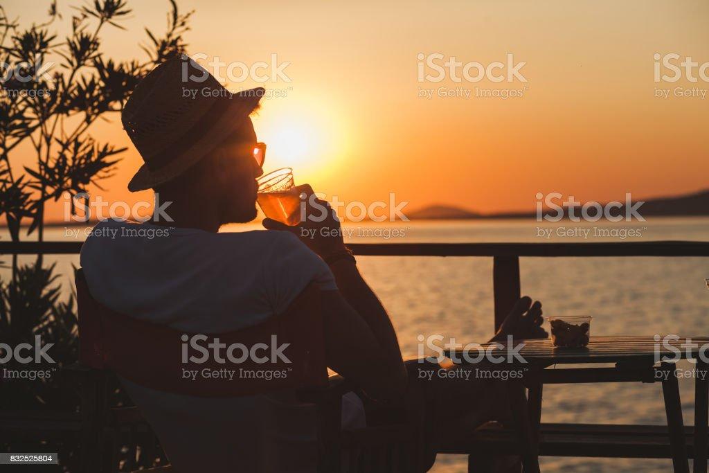 Young man enjoying sunset at a beach bar stock photo