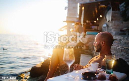 Portrait of a young man, sitting by the beach in an outdoors cafe in the Croatian seaside, Mediterranean. He is enjoying watching the sunset, having an espresso coffee in the dusk.