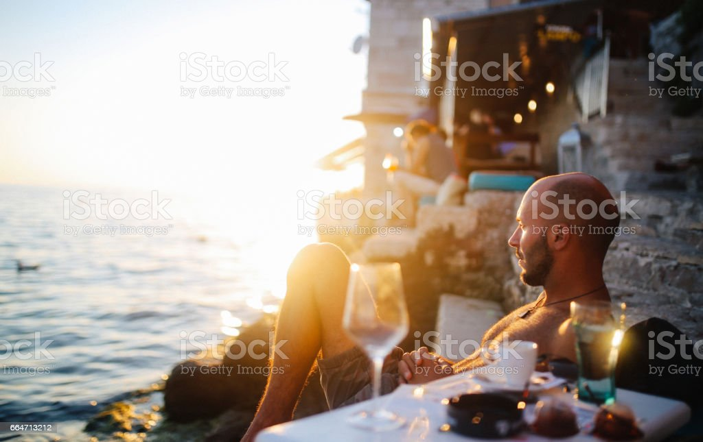 Young man enjoying the summertime by the sea stock photo