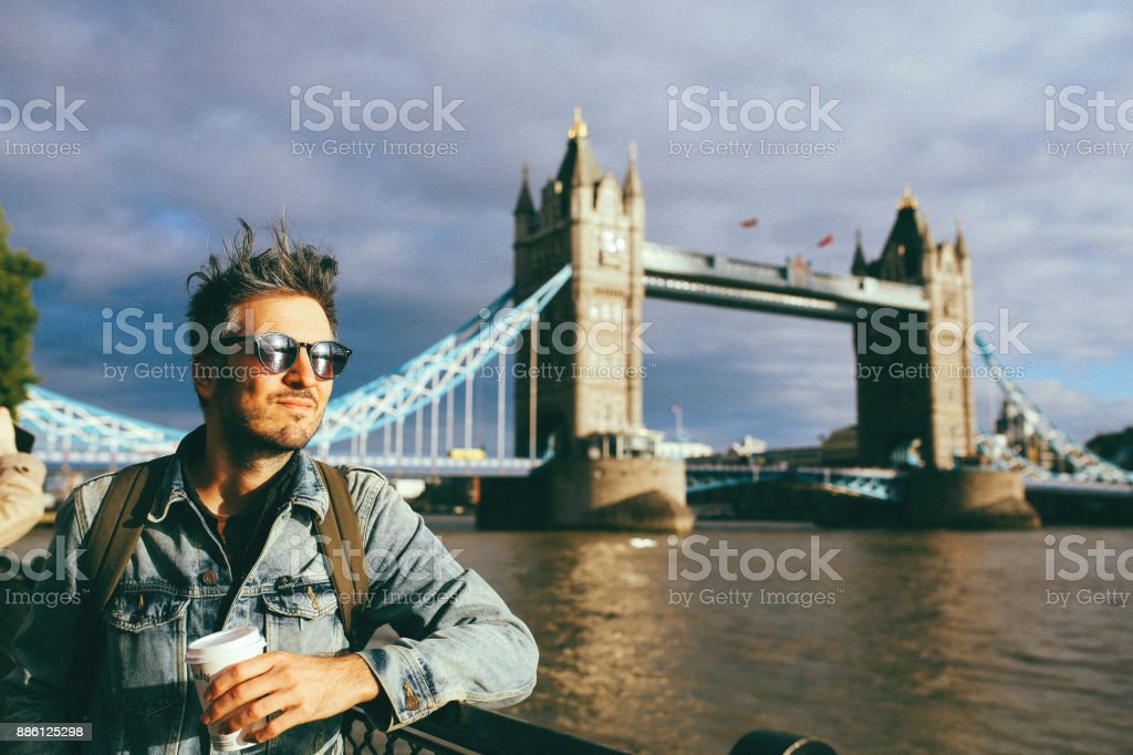Young man enjoying the view while having a coffee on the go, in London, UK stock photo