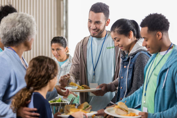 Young man enjoys serving meals at soup kitchen A young man stands in a volunteer serving line at his local soup kitchen and smiles as he passes out sandwiches. community center stock pictures, royalty-free photos & images
