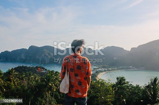 Vintage toned image of a young solo traveler man, wearing a colorful Hawaiian shirt, standing and enjoying the beautiful view over the Phi Phi islands in Thailand.