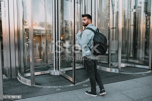 A young man with casual clothing and a backpack entering the revolving doors of an office building