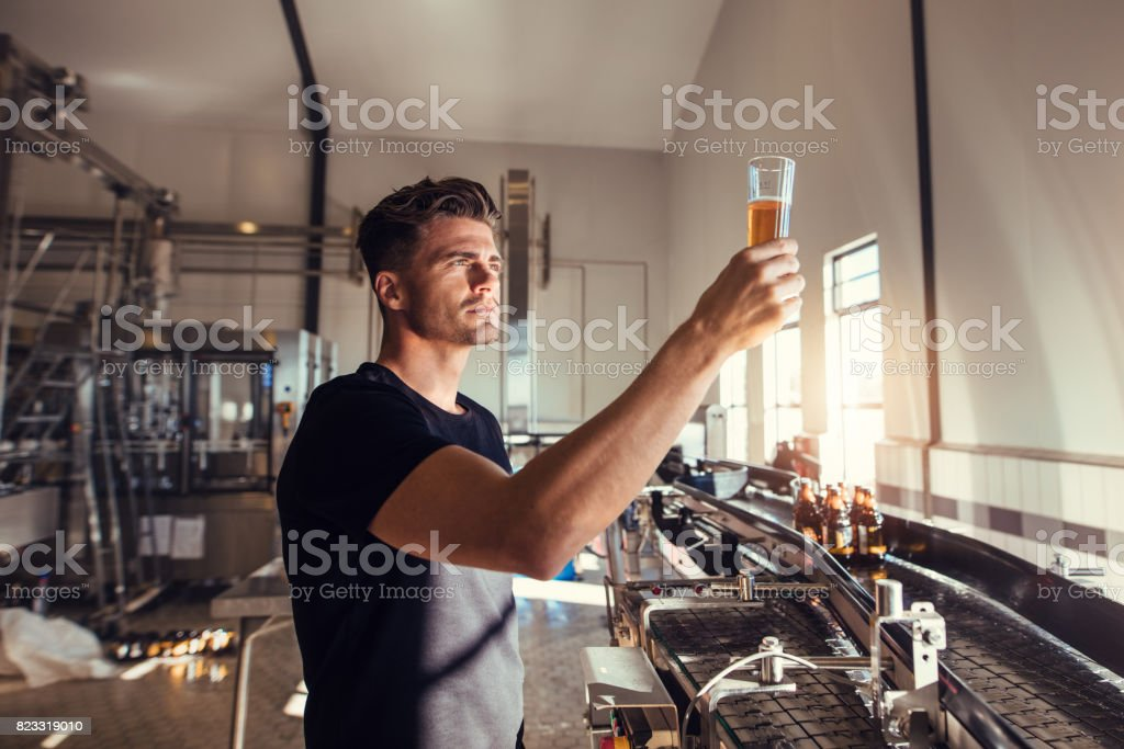 Young man examining the quality of craft beer at brewery stock photo