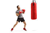 Full length shot of a young man exercising box with a red punching bag isolated on white background