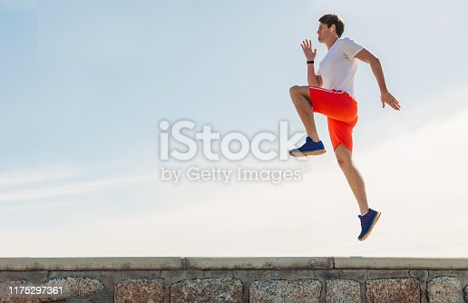Young man exercising by the sea, skipping in the spot.