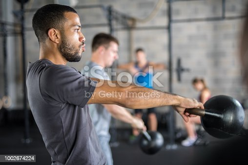 1069872470istockphoto Young man exercising in gym 1002674224