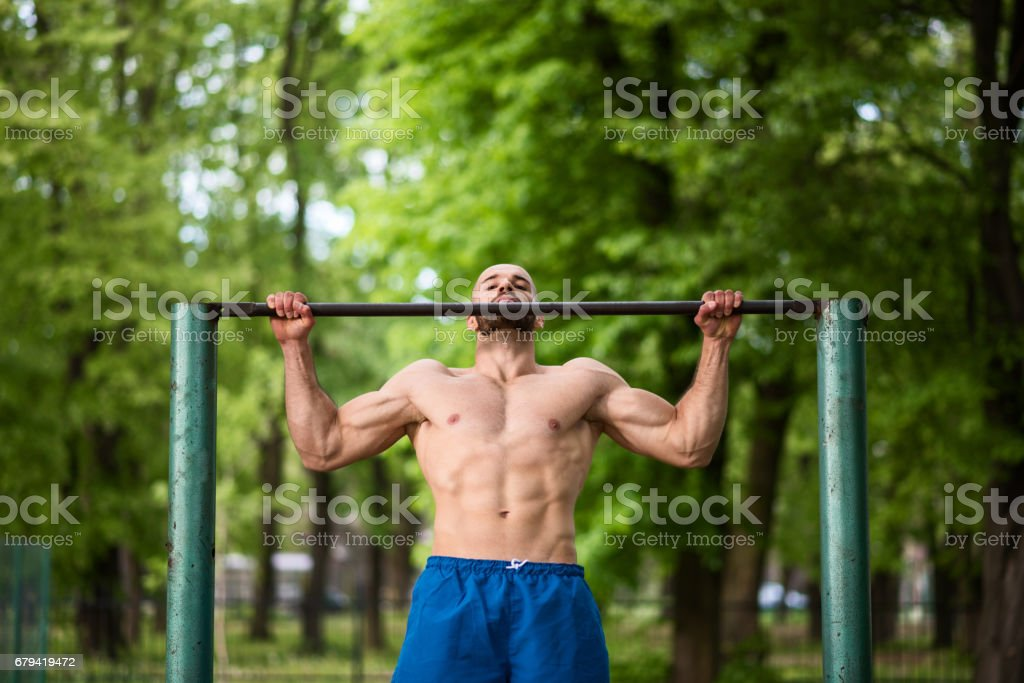 Young man exercising in nature, doing pull ups royalty-free stock photo
