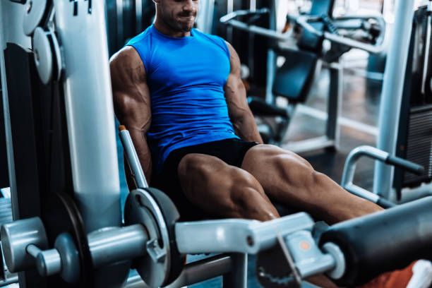 Young man exercising legs in the local gym Young man exercising legs exercise machine stock pictures, royalty-free photos & images