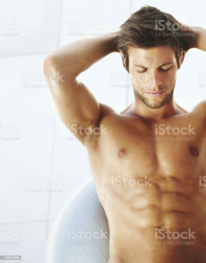 Young man exercising on fitness ball with hands behind head royalty-free stock photo