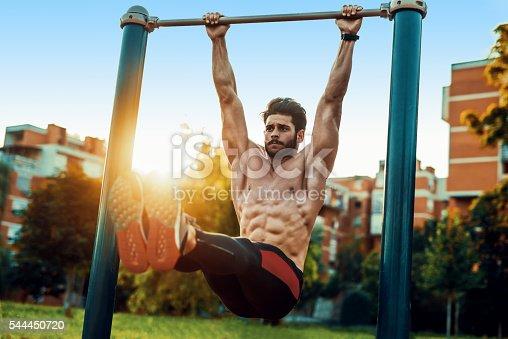 istock Young man exercising on horizontal bar outdoors 544450720