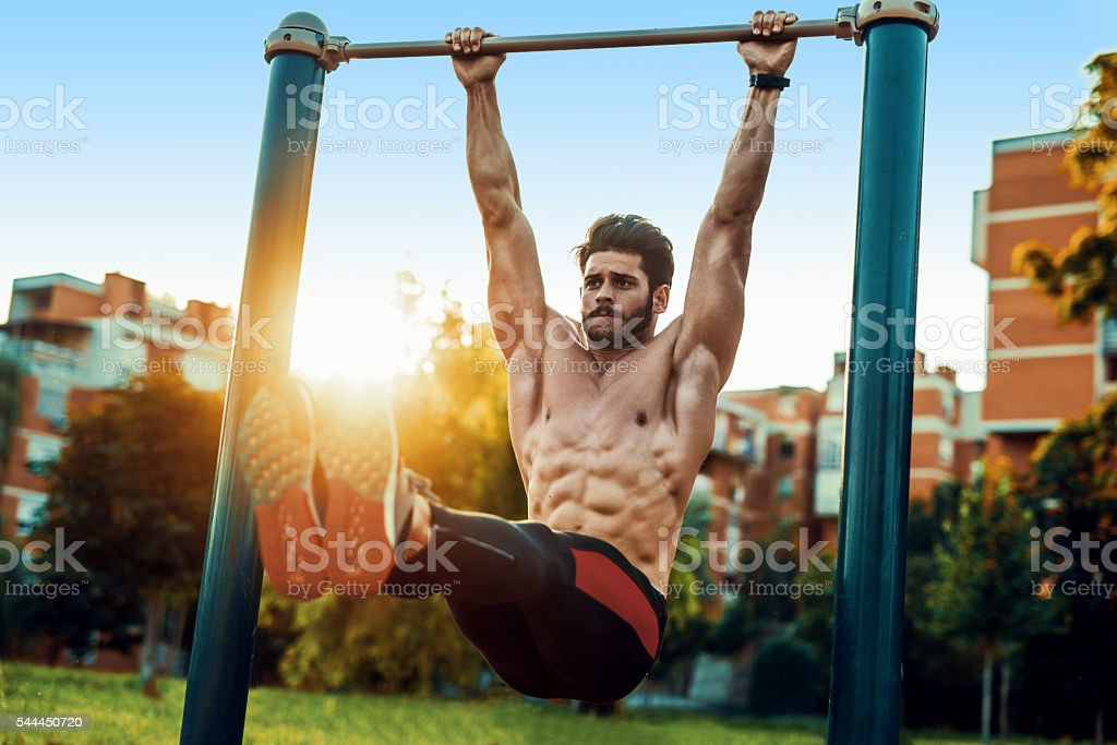 Young man exercising on horizontal bar outdoors stock photo