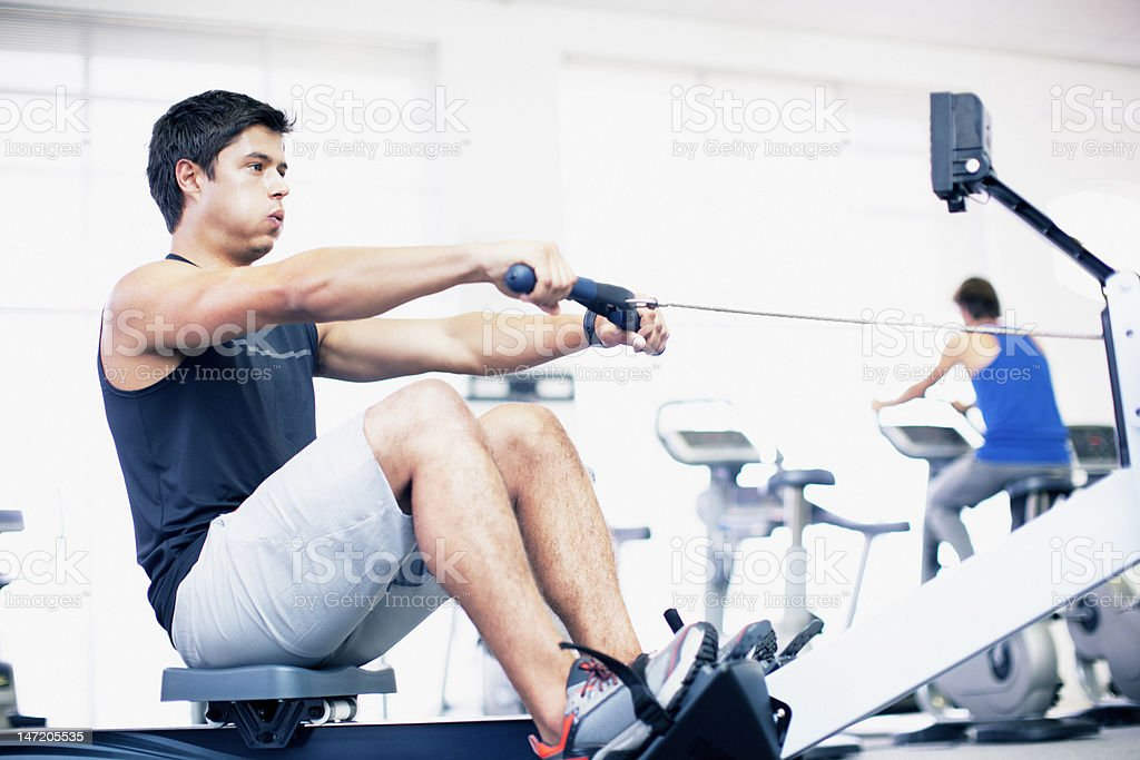 Young man exercising on rowing machine in gymnasium stock photo