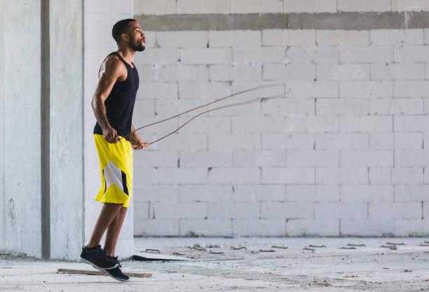 junger mann, der ausübung im freien - springseil stock-fotos und bilder