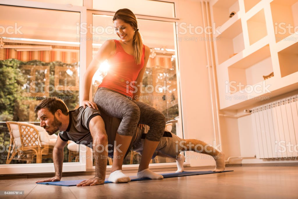Young man exercising push-ups with woman on his back. stock photo