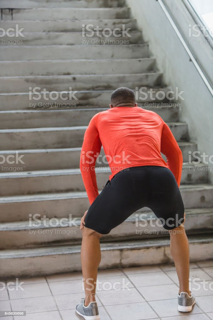 Young man exercising, resting at bottom of stairs stock photo