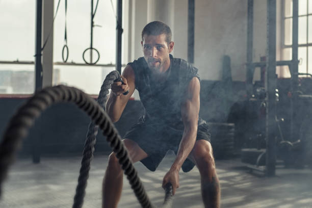 Young man exercising using battle rope stock photo