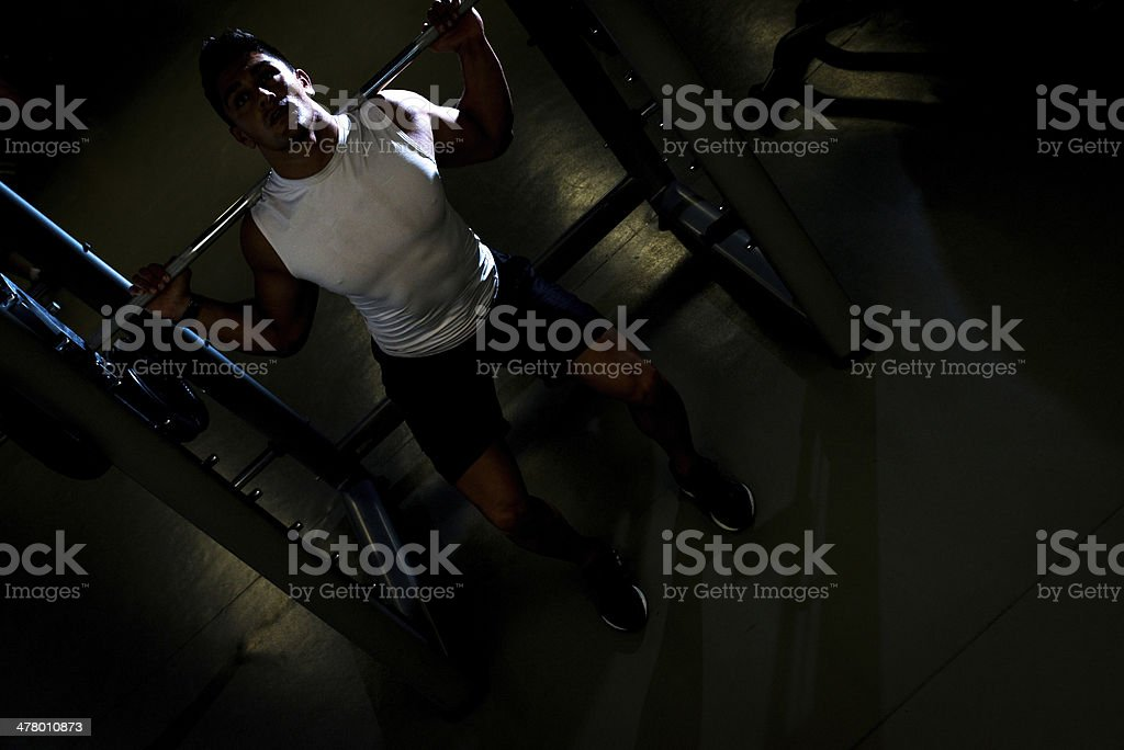 Young man exercising with barbell Squats royalty-free stock photo