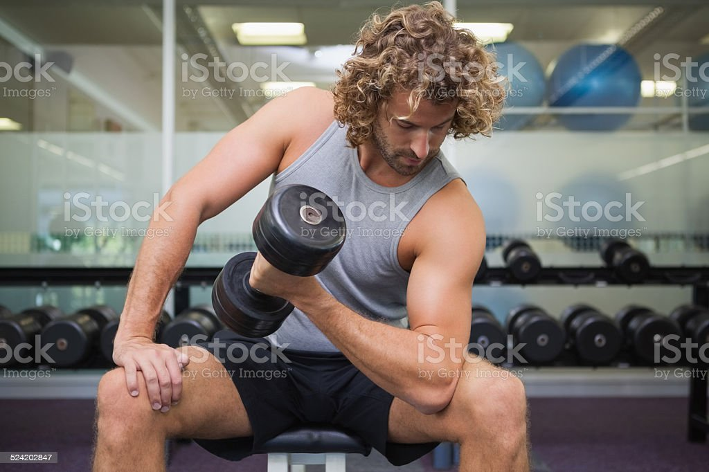 Young man exercising with dumbbell in gym stock photo