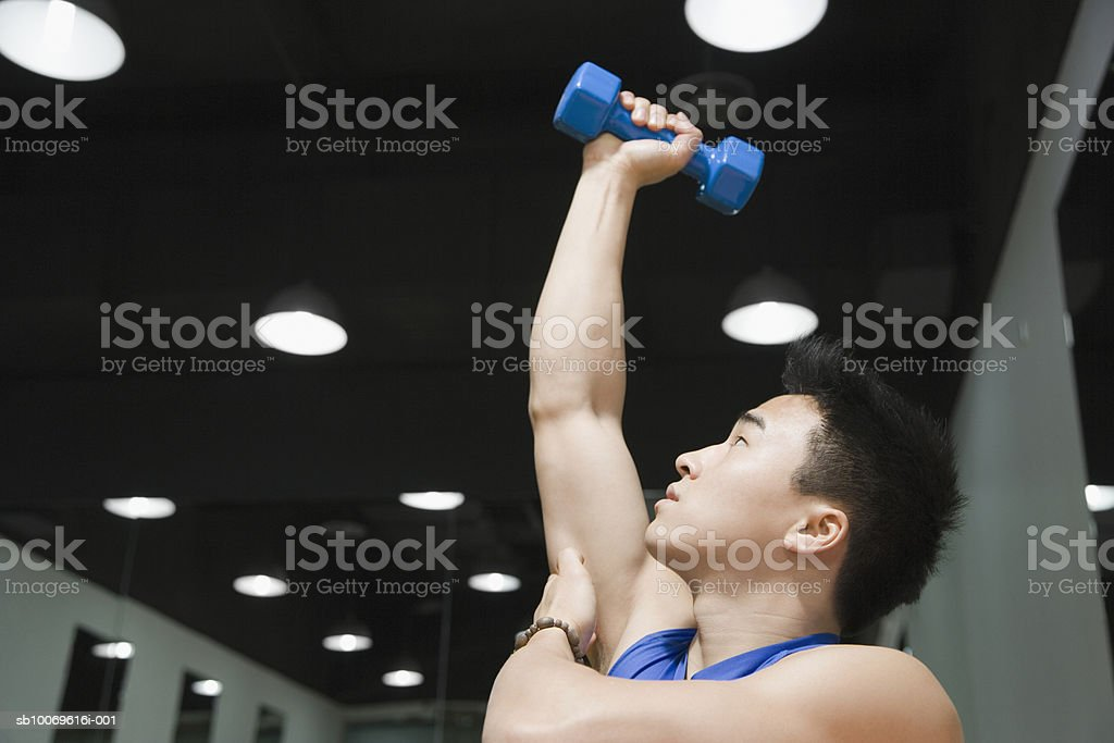 Young man exercising with hand weights, close-up royalty-free stock photo