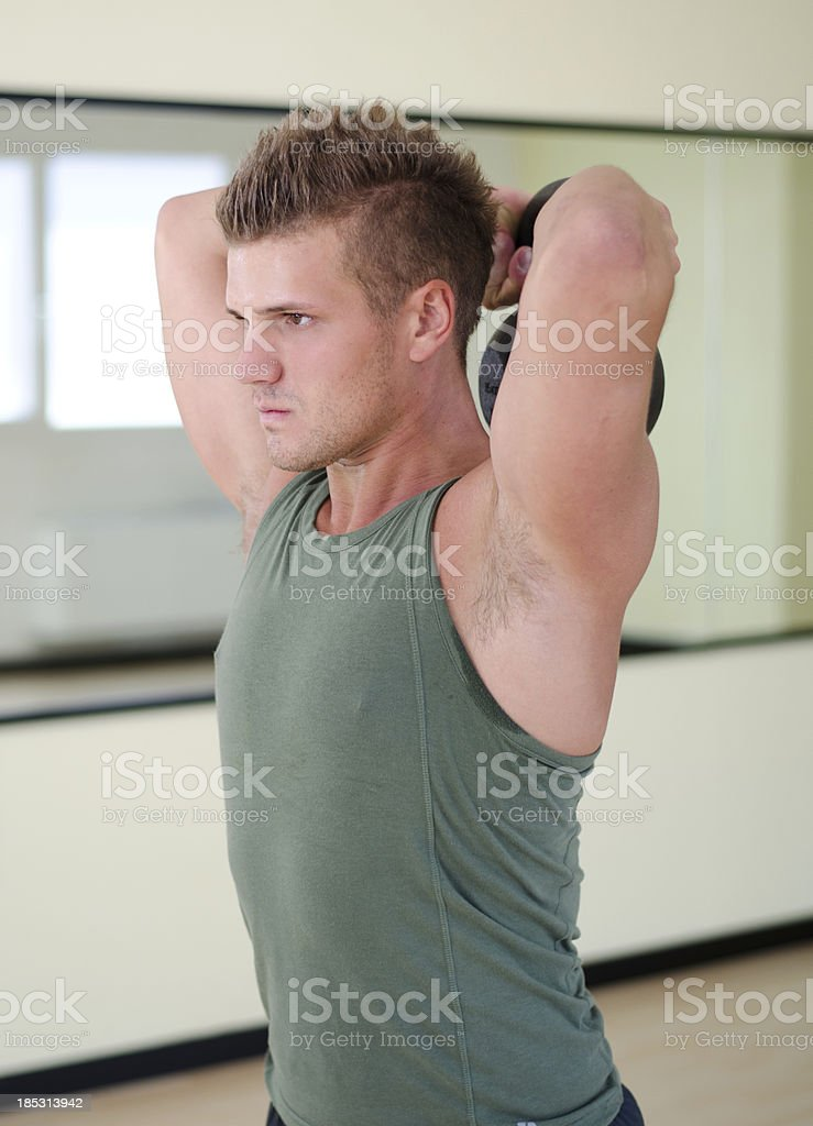 Young man exercising with kettlebell in gym royalty-free stock photo