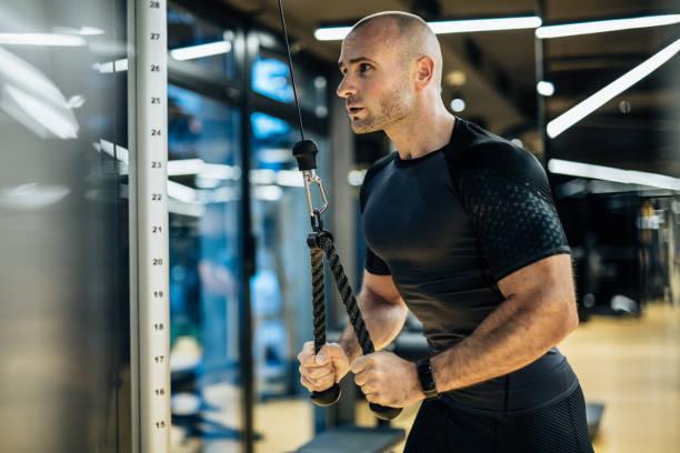 joven haciendo ejercicio con pesas en el gimnasio local - hombres grandes musculosos fotografías e imágenes de stock