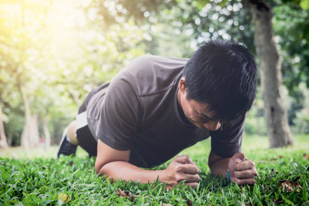 young man exercising workout fitness doing planking outside on grass  in summer park - peso mosca foto e immagini stock