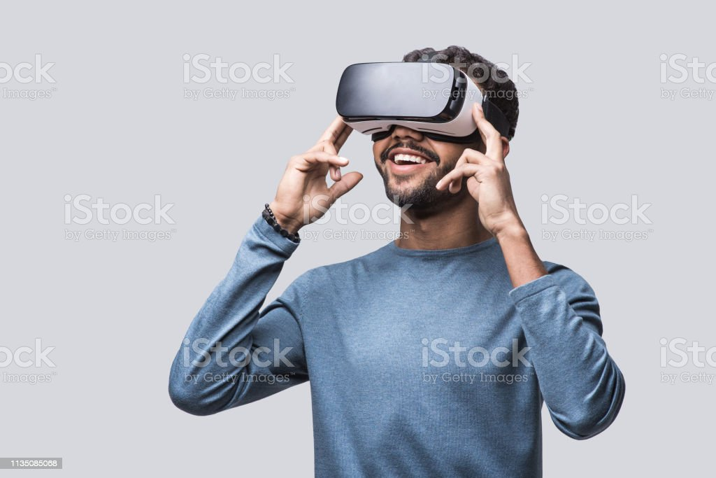 Young man experiencing virtual reality eyeglasses headset - Стоковые фото Белый роялти-фри
