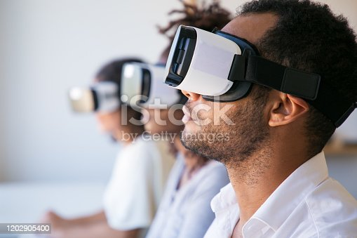 istock Young man experiencing VR headset at office 1202905400