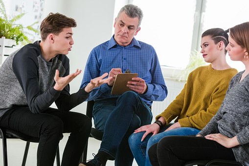 Young Man Explaining During Mental Group Therapy Stock Photo - Download Image Now