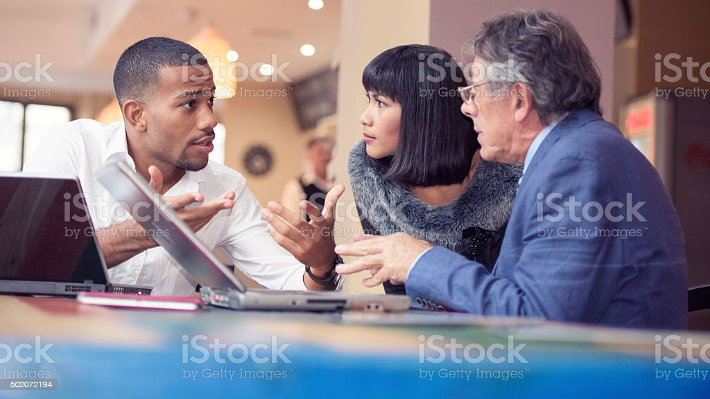 Young man explaining his business plans to his colleagues stock photo