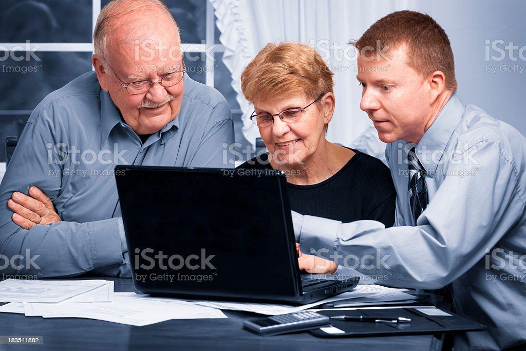 Young man explaining something on a laptop to senior couple stock photo