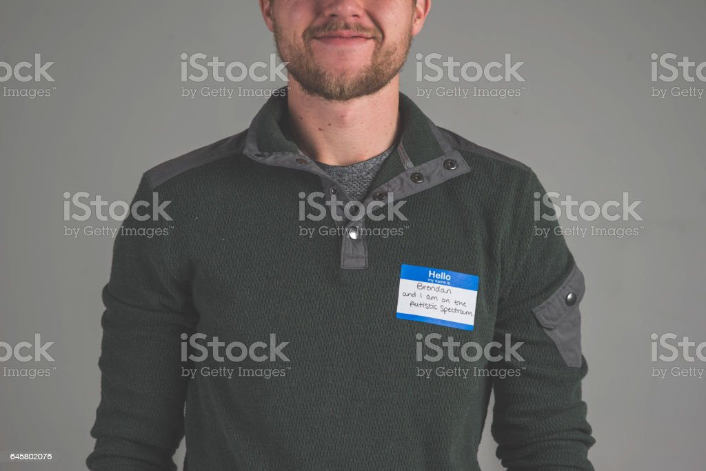 Young man facing audience with name tag that describes struggle 'autism' stock photo
